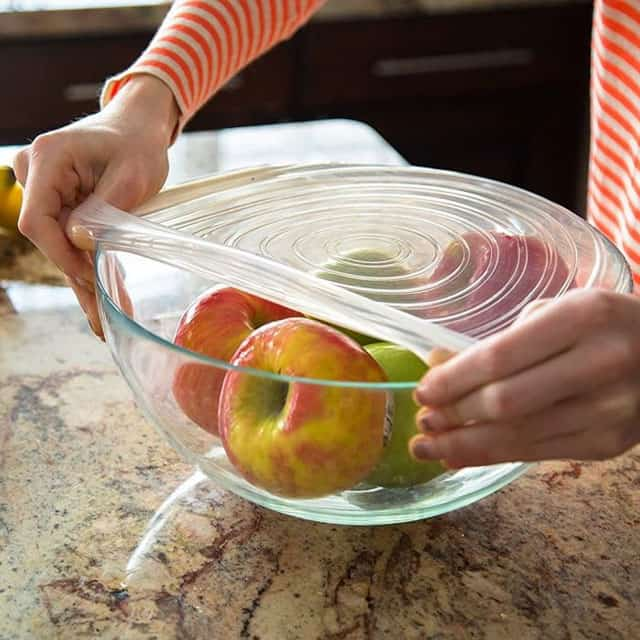 Closeup of woman hands placing stretch lid on a bowl of apples.