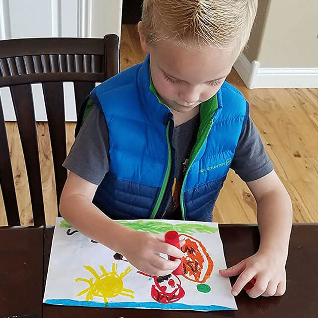 Boy coloring a sunny picture with modsticks.